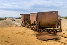 Old And Rusty Mine Carts In The Open Air On The Sand In Sardinia. Ingortosu's Mine. Arbus, Cagliari