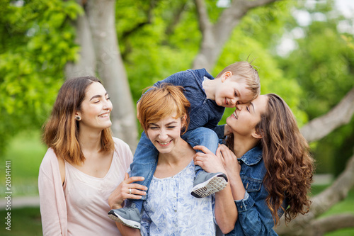 Foto  Happy young family enjoying free time in the park, mother, sisters and brother