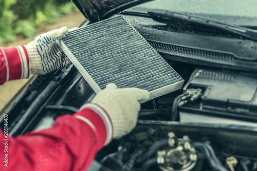 Fotografía  The auto mechanic replaces the car's interior filter.