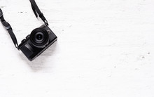 Black Camera On The Grunge White Wooden Background. Flat Lay Of Travel Accessories Background Concept.