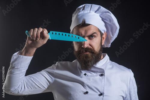 Bearded chef holds knife beside face Poster