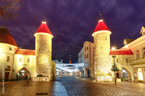 Decorated and illuminated Christmas Guard towers of Viru Gate and narrow street of Old Town at night, Tallinn, Estonia
