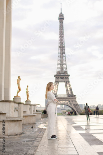Foto  Stylish woman in white overalls walking on Trocadero square near gilded statues and Eiffel Tower in Paris