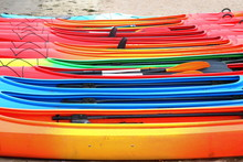 Many Bright Colored Kayaks On Sand Shore At Autumn Cloudy Day