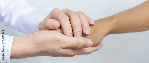 Fotografia  Two people holding hands for comfort