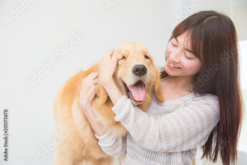 Photographie Asian beautiful woman playing with her dog and smiles at home