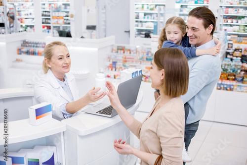 Let me see. Satisfied female pharmacist assisting family and posing in drugstore
