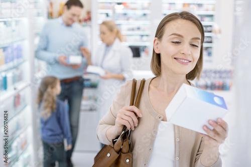 Fotobehang Apotheek Effective medication. Gay pretty woman smiling while picking up medication