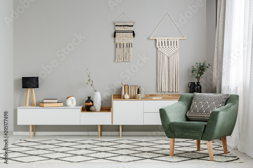 Fotobehang Zeilen Green armchair on patterned carpet in bright living room interior with decor on the wall. Real photo
