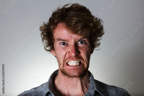 Valokuva  Angry young man with clenched teeth