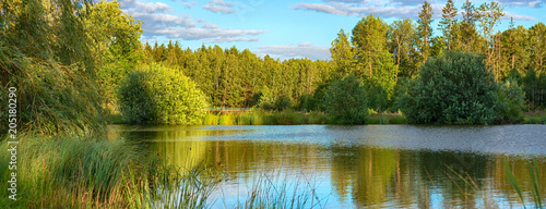 Calm river flowing gently through woodland landscape. Location Lagen in Belarus.Long banner