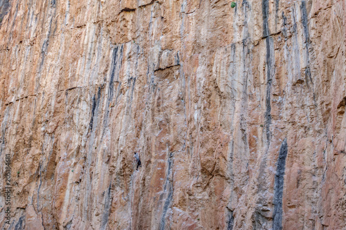 Poster Male climber hanging in the middle of a cliff