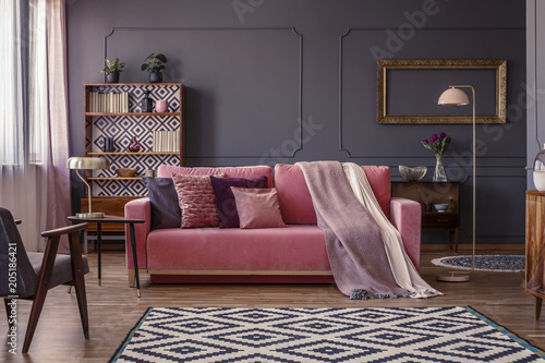 Fotobehang Wintersporten Pink velvet lounge with cushions and blanket standing in the middle of dark grey living room interior with molding on the wall, geometric carpet and two metal lamps