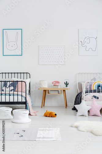Fotobehang Stof Wooden table between black and white bed in children bedroom interior with posters. Real photo