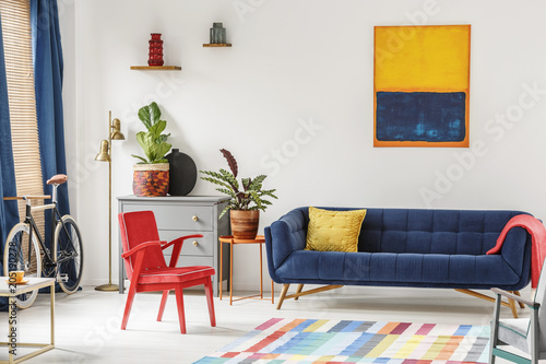 Red Chair And Royal Blue Lounge Placed In Bright Sitting Room