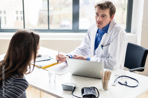Fototapety, obrazy: High angle view of a young physician listening to his patient with respect and dedication, during a private consultation in the office of a modern medical center