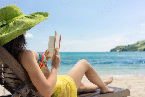 Poster Vissen Side view of a young beautiful woman reading a book while sitting on a wooden lounge chair at the beach in a sunny day during summer vacation in Flores Island, Indonesia