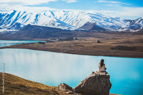 In de dag Oceanië A girl with long hair sit on a rock in Mt. John looking at Lake Tekapo