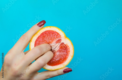 Fotografia  Two fingers on grapefruit on blue background. Sex concept.