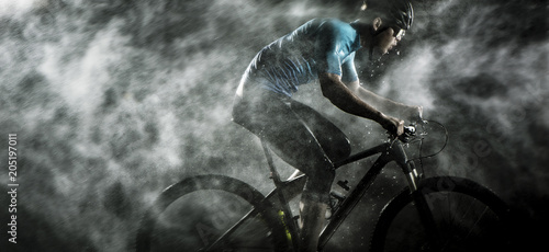Cyclist cycling on mountain bike with rainy ,foggy on black background.