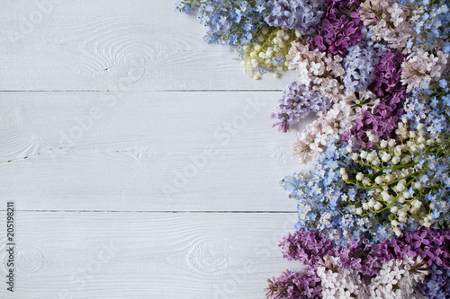 Foto op Aluminium Lilac Spring flowering branches of lilac, flowers of lilies of the valley and forget-me-nots on a wooden background