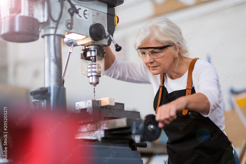 Fototapety, obrazy: Senior woman doing woodwork in a workshop