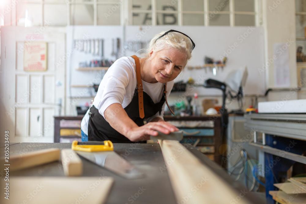 Fototapety, obrazy: Senior woman doing woodwork in a workshop