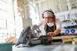 Senior female carpenter working with a circular saw