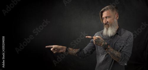 Valokuva  Portrait eines bärtigen tätowierten Mannes, vor schwarzem Hintergrund