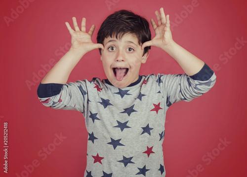 Valokuva niño gracioso que saca la lengua sobre fondo rojo