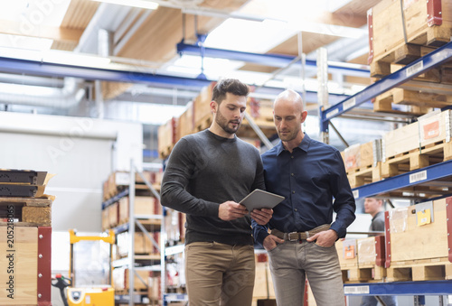 Two men with tablet talking in factory storeroom