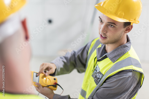Electricians working with voltmeter on construction site