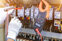 Electrician Measurements With Multimeter Tester In Control Panel.