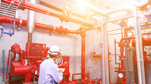 Obraz Engineer check red generator pump for water sprinkler piping and fire alarm control system. - fototapety do salonu