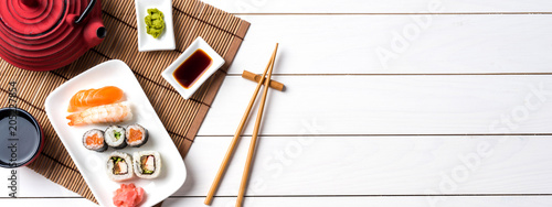 Poster Sushi bar Set of sushi with red teapot and chopsticks. Top view
