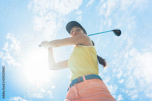 Fotobehang Zeilen Low-angle view of a female professional player holding up the iron club with concentration for strike while playing golf outdoors against cloudy sky