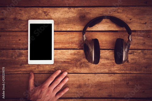 Papiers peints A top view of a set of wireless headphones and blank tablet template lying on a rustic wood table, desk. Styling and grain effect added to image.