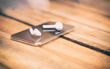 A 45 Degree View Of A Set Of Wireless Earbud Headphones And Mobile Phone Lying On A Rustic Wooden Table. Styling And Grain Effect Added To Image.