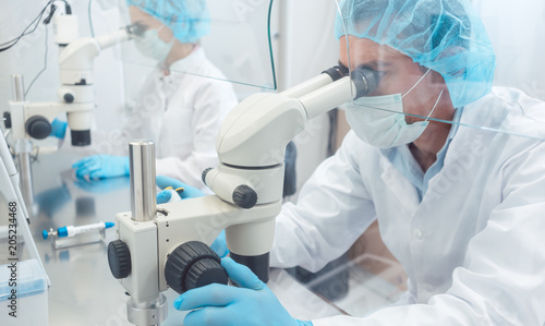 Two lab technicians or scientists working in laboratory looking thru microscopes