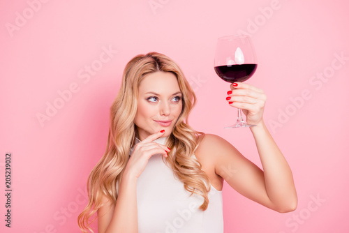 Foto op Plexiglas Alcohol Portrait of ponder minded, expert, elegant pretty girlfriend looking at raised glass with alcohol beveragein hand with evaluative view isolated on pink background