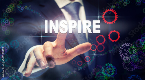 Photo  A businessman pressing a Inspire business concept on a graphical display of cogs