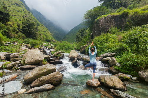 Stickers pour porte Gris traffic Woman in yoga asana Vrikshasana tree pose at waterfall outdoors