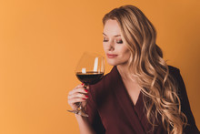 Portrait Of Dreamy Lovely Cute Woman With Close Eyes Holding Glass With Red Wine In Hand Enjoying Smell Of Beverage Having Fun Isolated On Dark Yellow Background