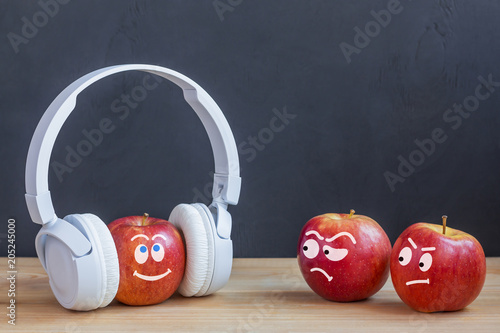 One apple in wireless headphones listening to music, two apple envy him Fototapeta