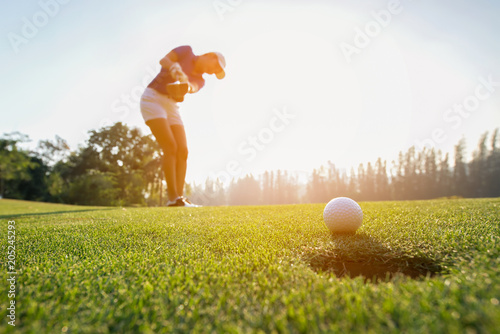 Door stickers Golf Golfer asian woman focus putting golf ball on the green golf on sun set evening time.. Healthy and Lifestyle Concept