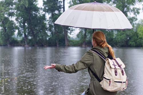 Plakat Kobieta z parasolem i plecak stojący w deszczu na riverside