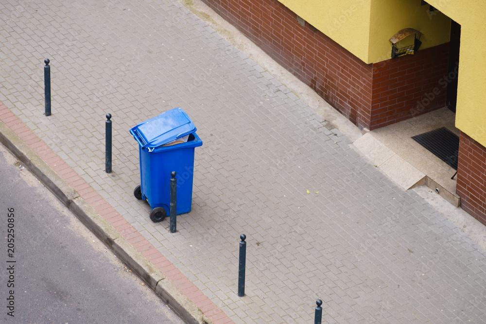 Fototapeta Blue trash can on street pavement
