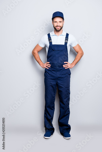 Full size fullbody portrait of attractive cheerful deliver in blue uniform with stubble looking at camera holding two hands on waist, isolated on grey background Wall mural