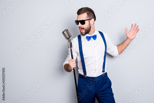 Portrait of handsome attractive singer in blue pants with suspenders and black g Canvas-taulu