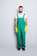 Full size fullbody portrait of handsome attractive bearded concentrated housekeeper with stubble, hairstyle in green uniform, isolated over grey background